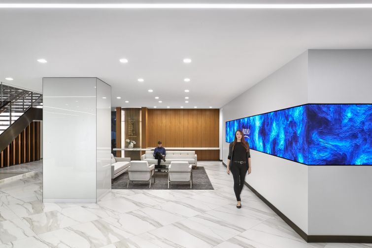 Common spaces include wood panelling, marble-like porcelain tile, and moving video walls.