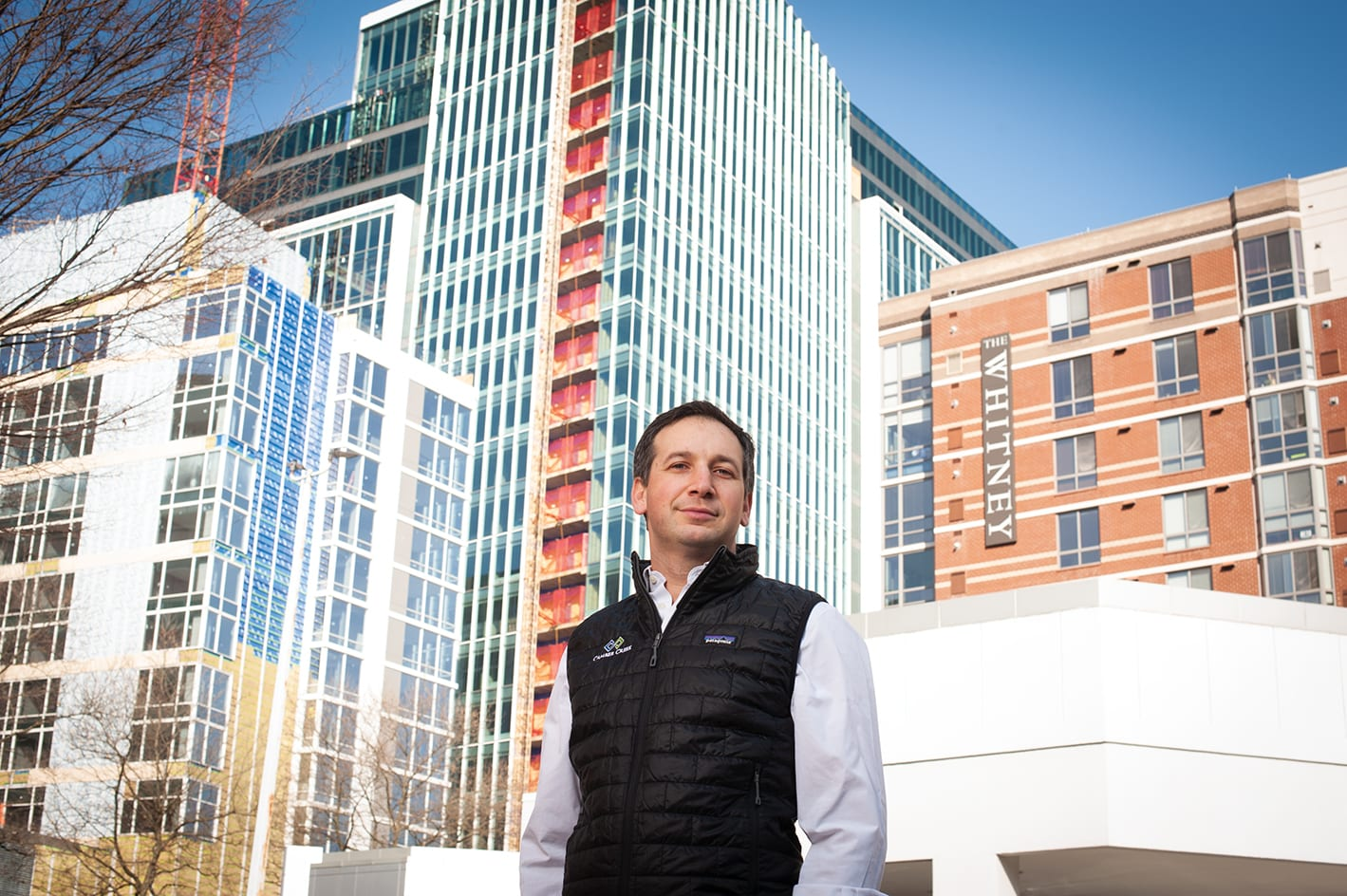 A man standing outside with buildings in the background.