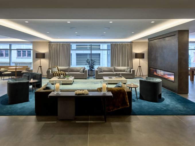 The new 11,000-square-foot amenity center at 100 Park Avenue, designed by Design Republic, includes several different areas, including a lounge space with midcentury modern-inspired furniture.