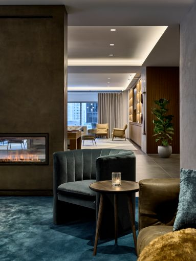 "The lounge includes a freestanding faux fireplace (the ""fire"" is created by a spray of water and LED lighting) that helps divide the space."