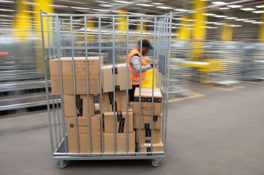 An Amazon sorting employee pulls a cart with parcels in a distribution center.