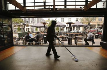 """Part of the sanitation team cleaning a restaurant as they prepare to open for indoor dinning. In the """"red tier,"""" counties are allowed to reopen indoor dining and gyms."""