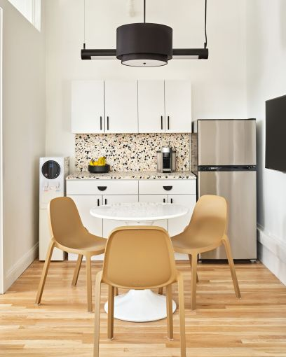 Recycled chairs, a white tulip table and a terrazzo backsplash and counter help give the new kitchen a midcentury modern touch.