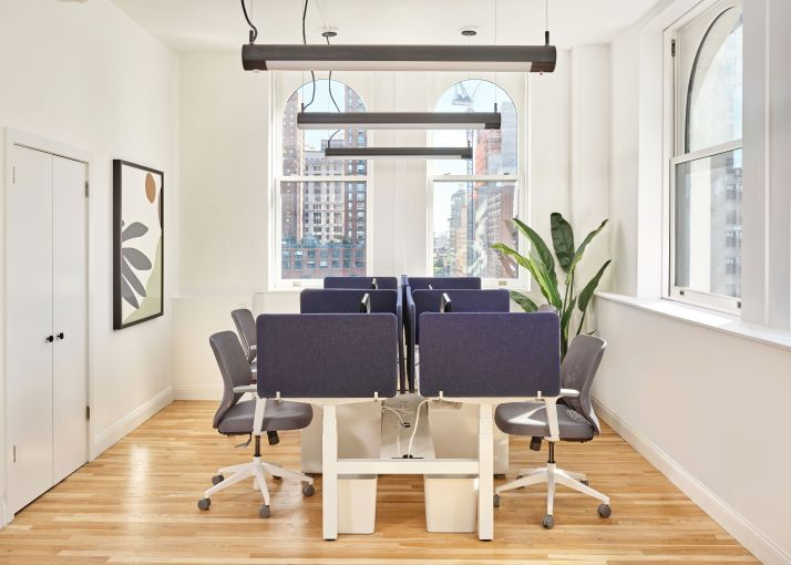 The new 1,000-square-foot office has a small open work area framed by loft windows.