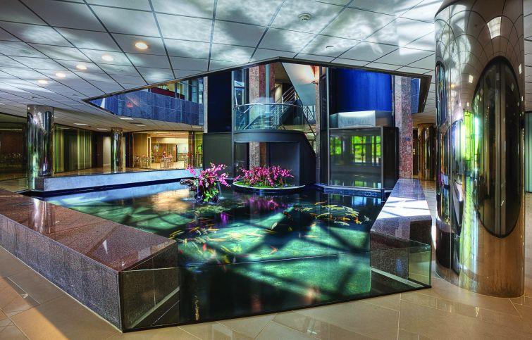 A pond with fish inside a building lobby.