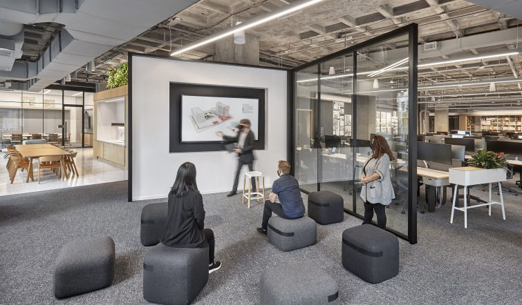 """One of the studio's many presentation spaces is the """"The Cube,"""" a semi-open meeting room with a glass wall."""