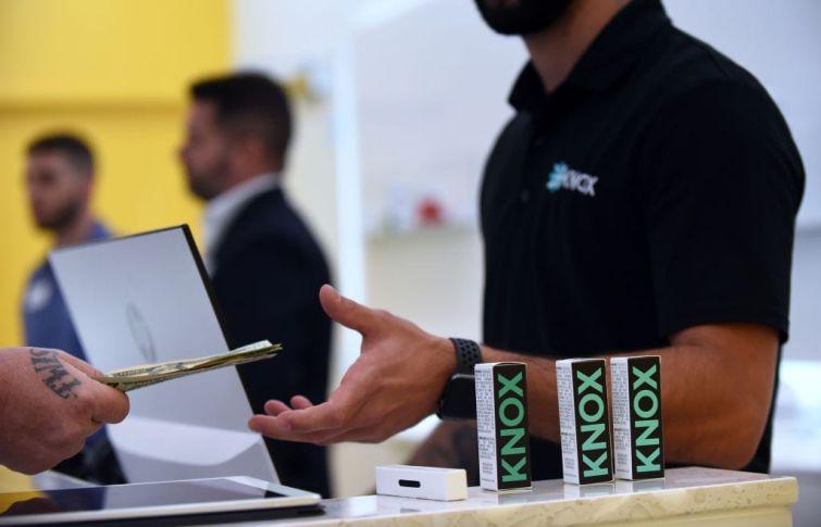 A patient pays for an order of medical marijuana at a new Knox medical marijuana dispensary in Florida.