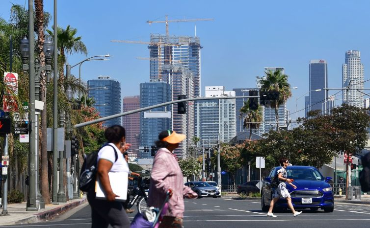 Pedestrians cross a street against a backdrop of luxury highrise apartments under construction in Los Angeles