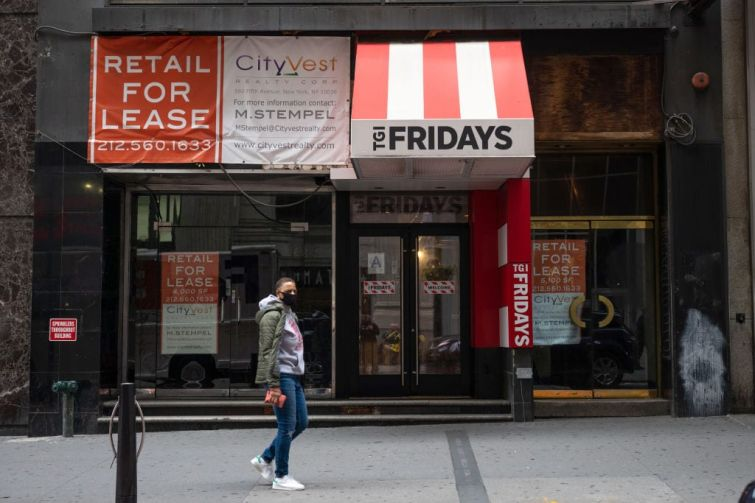 A person wearing a mask walks past a For Lease sign at a closed down TGI Fridays in the Financial District on October 22, 2020 in New York City.