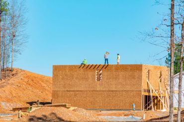 Workers stand a top a new house in Alabama.