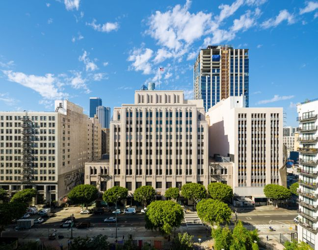 The historic Trust Building is a large grey art deco building located in downtown Los Angeles.