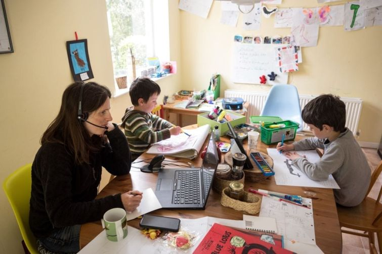 A mother works from surrounded by a children at a cluttered desk.