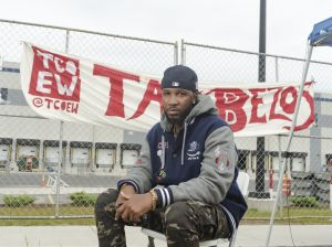 """Chris Smalls sits in front of a sign reading """"Tax Bezos."""" Smalls has been organizing for an independent Amazon Labor Union since he led a protest advocating for stronger coronavirus safety precautions at the company's Staten Island facility."""