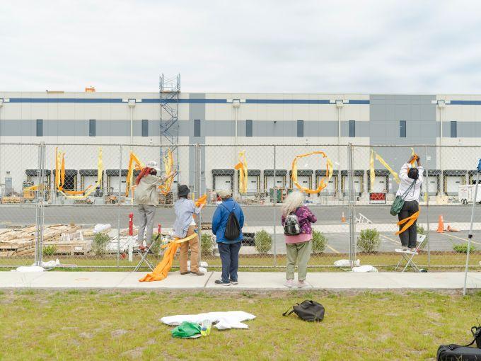 "A group of union advocates write ""Union"" onto a fence erected around Amazon's JFK8 Staten Island Warehouse."