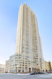 A large white and glass building jutting into an empty blue sky.