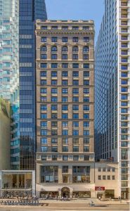 A 20-story Manhattan building made of grey stone and small-ish windows.