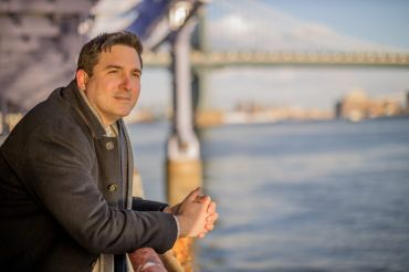 Ben Kallos overlooks the East River on a sunny day in New York. A bridge is visible behind him.