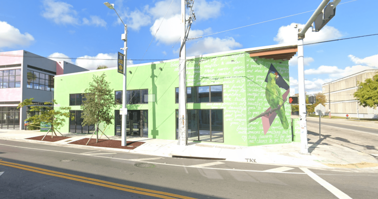 An empty lime green building sits on an empty intersection surrounded by blue skies with a few clouds.