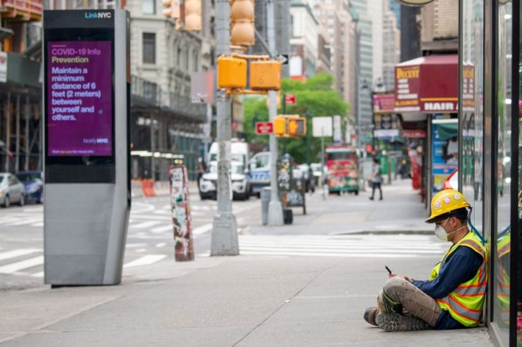"""A construction worker wearing a mask sits on the street near a """"COVID-19 info"""" digital display on May 28, 2020 in New York City."""