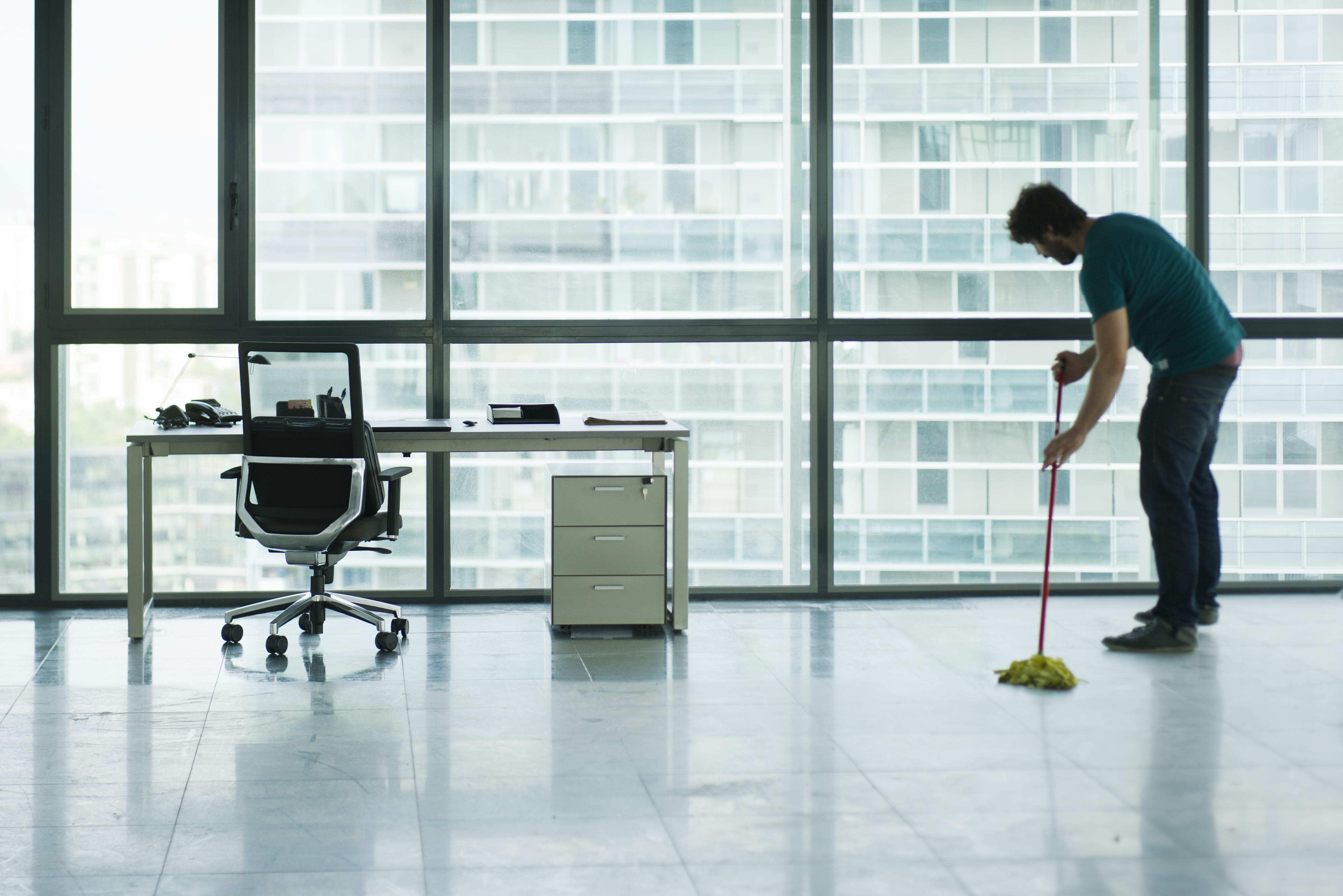 A lone man mopping an office floor.
