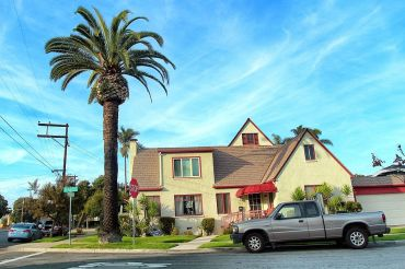 a suburban yellow and red home near a palm tree.