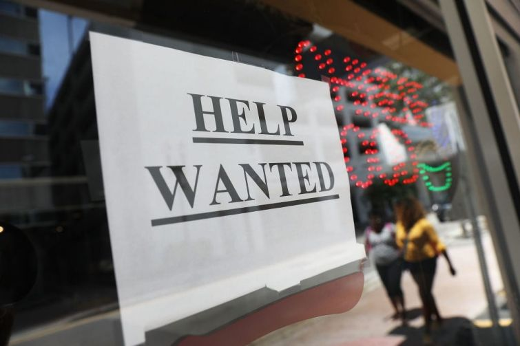 """A """"help wanted"""" sign hangs on a window of a restaurant in Miami, Florida."""