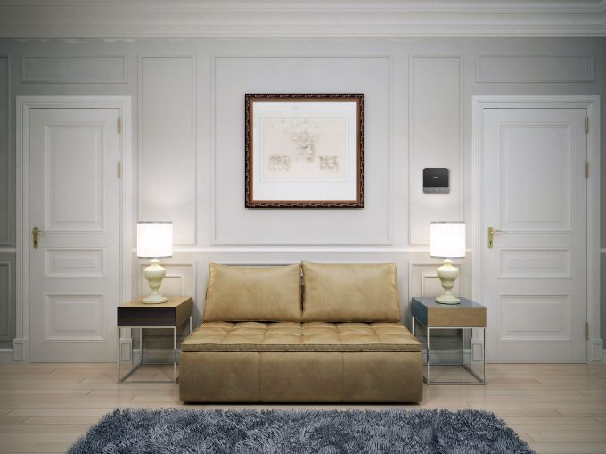 An apartment with a yellow, centered couch and two lamps on either side.