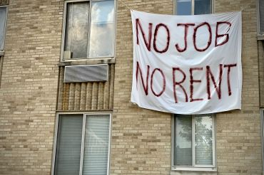 A banner against renters eviction reading no job, no rent is displayed on a controlled rent building in Washington, DC.