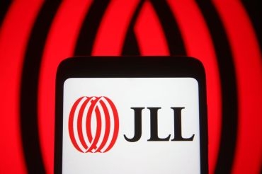 In this photo illustration the Jones Lang LaSalle Incorporated (JLL) logo of a global commercial real estate services company is seen on a smartphone and a pc screen.
