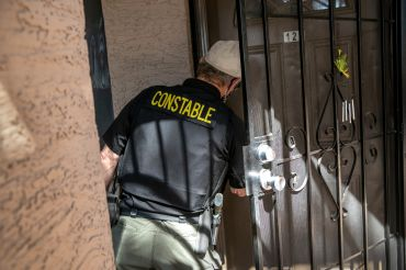 """A man in a vest that says """"constable"""" knocking on a door."""