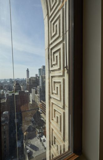 The half-moon windows are set into carved plaster and terra cotta elements that are being restored.