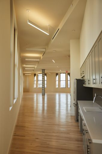 The 19th floor has been renovated into a marketing center with a modern gray and black office kitchen.