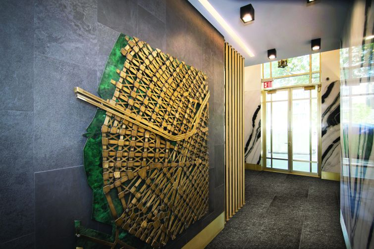 The lobby includes Williamsburg-themed brass sculptures by Kenneth Nilson, such as this wall map.