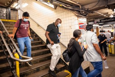 People in masks walking down subway steps.