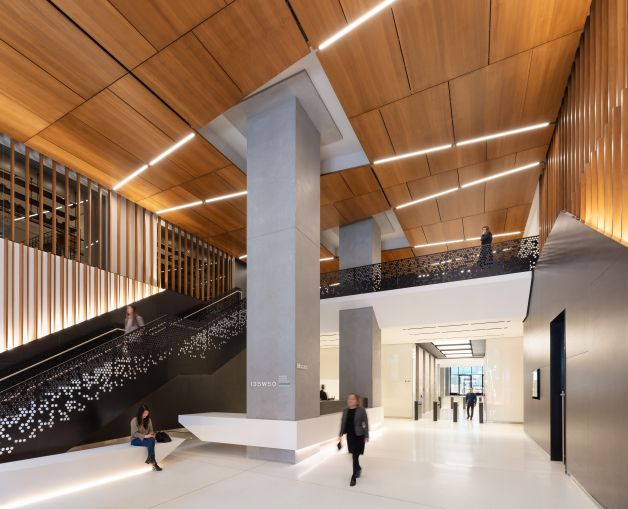 The new lobby is double height and includes a wood paneled ceiling and reinforced columns that were integrated into the new reception desk.