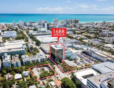 A building and two parking lots highlighted in red with a backdrop of an aerial view of Miami Beach.