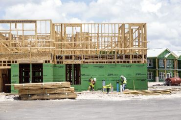 Construction workers beneath a large wood frame of a building.