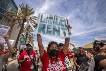 A woman calls for rent relief as a coalition of activist groups and labor unions participate in a May Day march for workers' and human rights earlier this year.