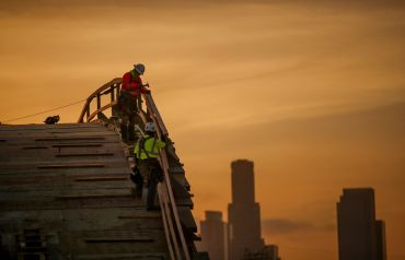 With a view of the Los Angeles skyline at sunset, a construction crew works on the Sixth Street Viaduct Replacement Project that crosses the 101 Freeway and Los Angeles River. The bridge is an on-going $588 million replacement project scheduled for completion in Summer of 2022.