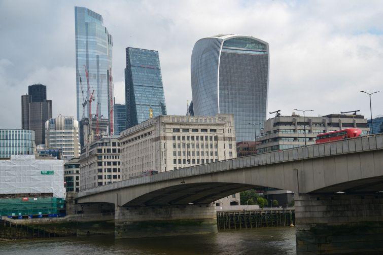 A city skyline beyond a concrete bridge over a river.