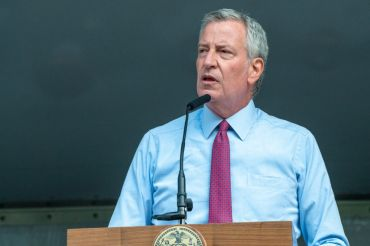 New York City Mayor Bill DeBlasio stands at a podium with a grey background behind him.