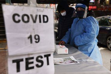 """A sign saying """"COVID 19 TEST"""" in front of a healthcare worker adorned in a face shield and blue suit."""