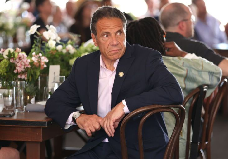 Governor of New York Andrew Cuomo sits at a decorated table at the Tribeca Festival looking off to the right, while figures in the background have their backs turned to him.