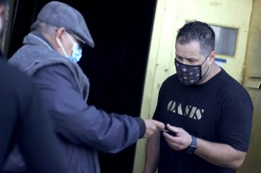 A doorman at Oasis checks a customer's vaccination card before allowing him to enter on July 29. As COVID-19 begins to surge due to the Delta variant, The San Francisco Bar Owner Alliance, which consists of over 500 bars in San Francisco, is implementing a new policy that requires bar customers to show proof of vaccination or a negative COVID-19 test within 72 hours of the bar visit.