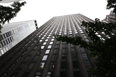 A tall building soaring toward the sky and viewed from the street.