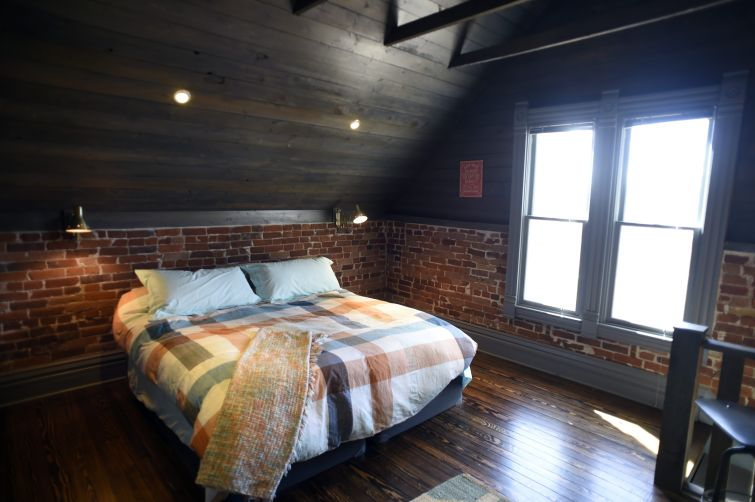 A very clean room with a brick wall and a bed.