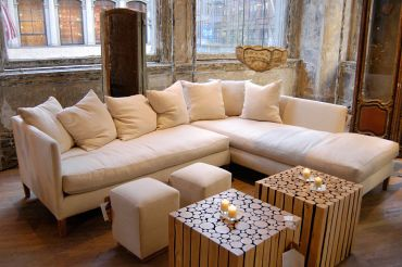 A white couch with fluffy pillows centered in a photo with wooden tables and candles on top.