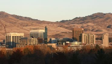A skyline of squat buildings with mountains behind.