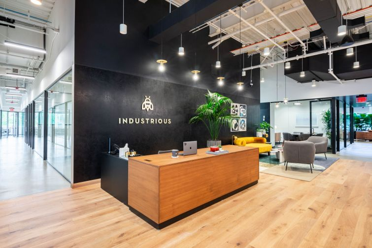 A modern office with black walls and Industrious' logo printed on the back wall behind a front desk.