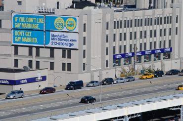 A big billboard next to a highway.